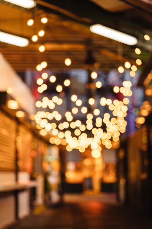 Bokeh glowing lights of lamps hanging on blurred background of urban street at late evening