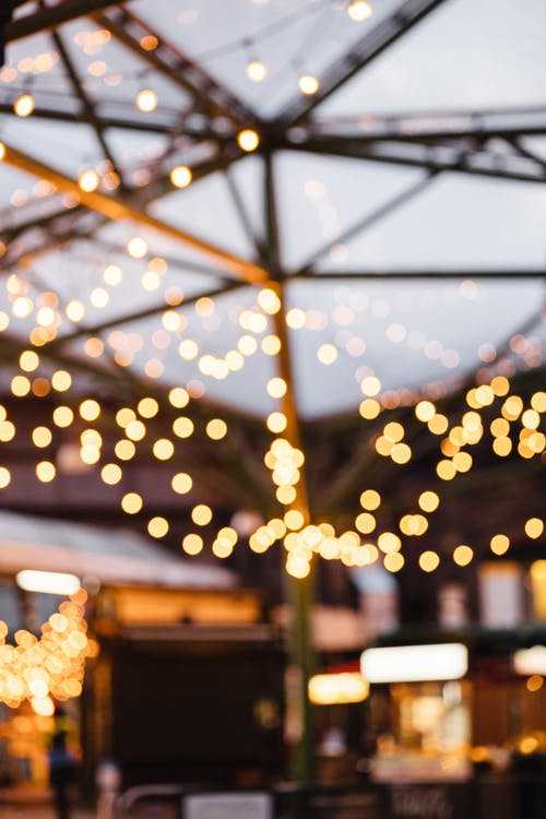 Many shimmering round lights of garland under ceiling of cafe on blurred background