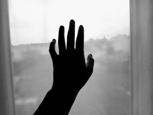 Silhouette of crop person touching window with hand indoors