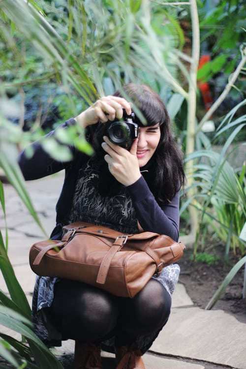 Woman Taking Picture While Holding Brown Leather Bag