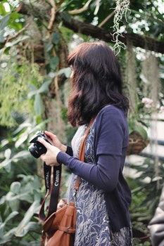 Woman in Blue Cardigan Holding Canon Dslr Camera