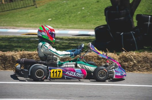 Man In Racing Suit With Helmet Riding Go Kart