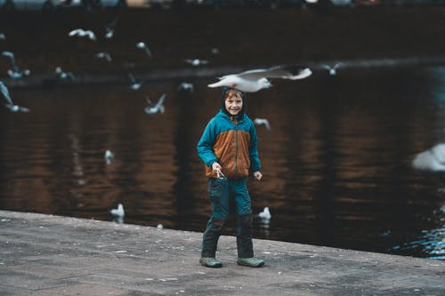 Full body of positive boy with slingshot playing on embankment of rippling pond with flying seagulls