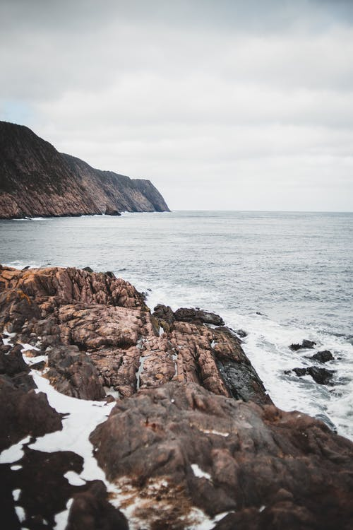 Stony shore with rough cliff washed by water of foamy ocean under cloudy gray sky