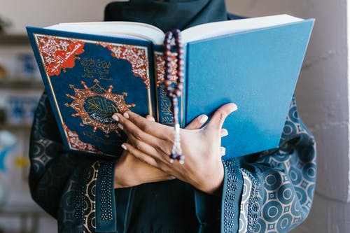 Person Holding Blue Holy Book