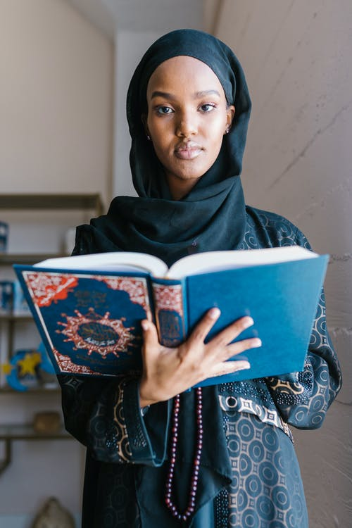 Woman in Black Hijab Holding White Book
