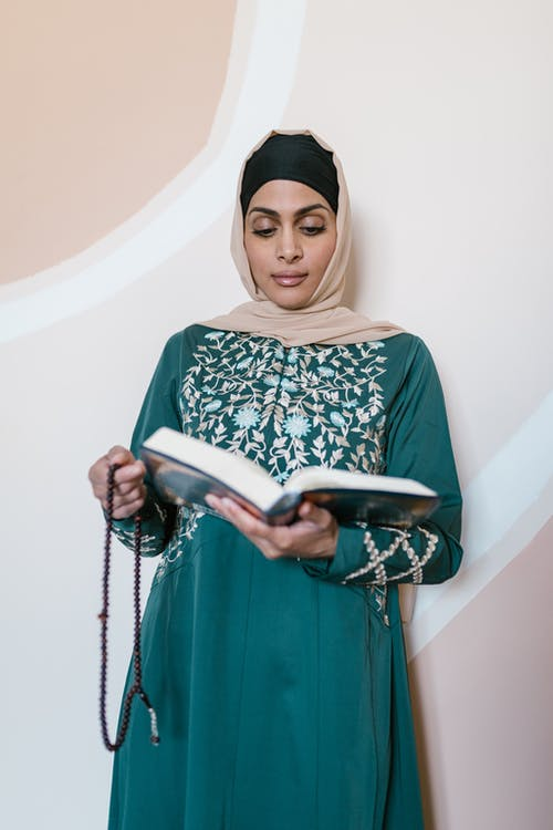 Woman in Green and White Hijab Holding A Holy Book
