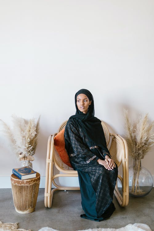Woman in Black Hijab Sitting on White Chair