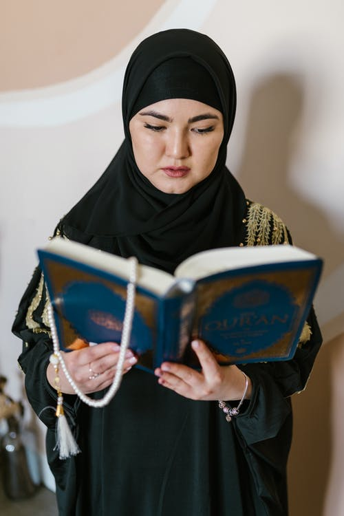 Woman in Black Hijab Holding Blue and White Book
