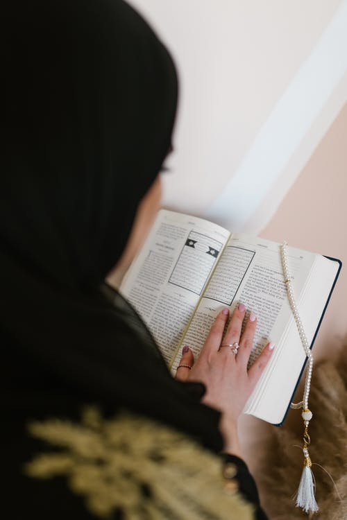 Person in Black Hijab Holding White Printer Paper