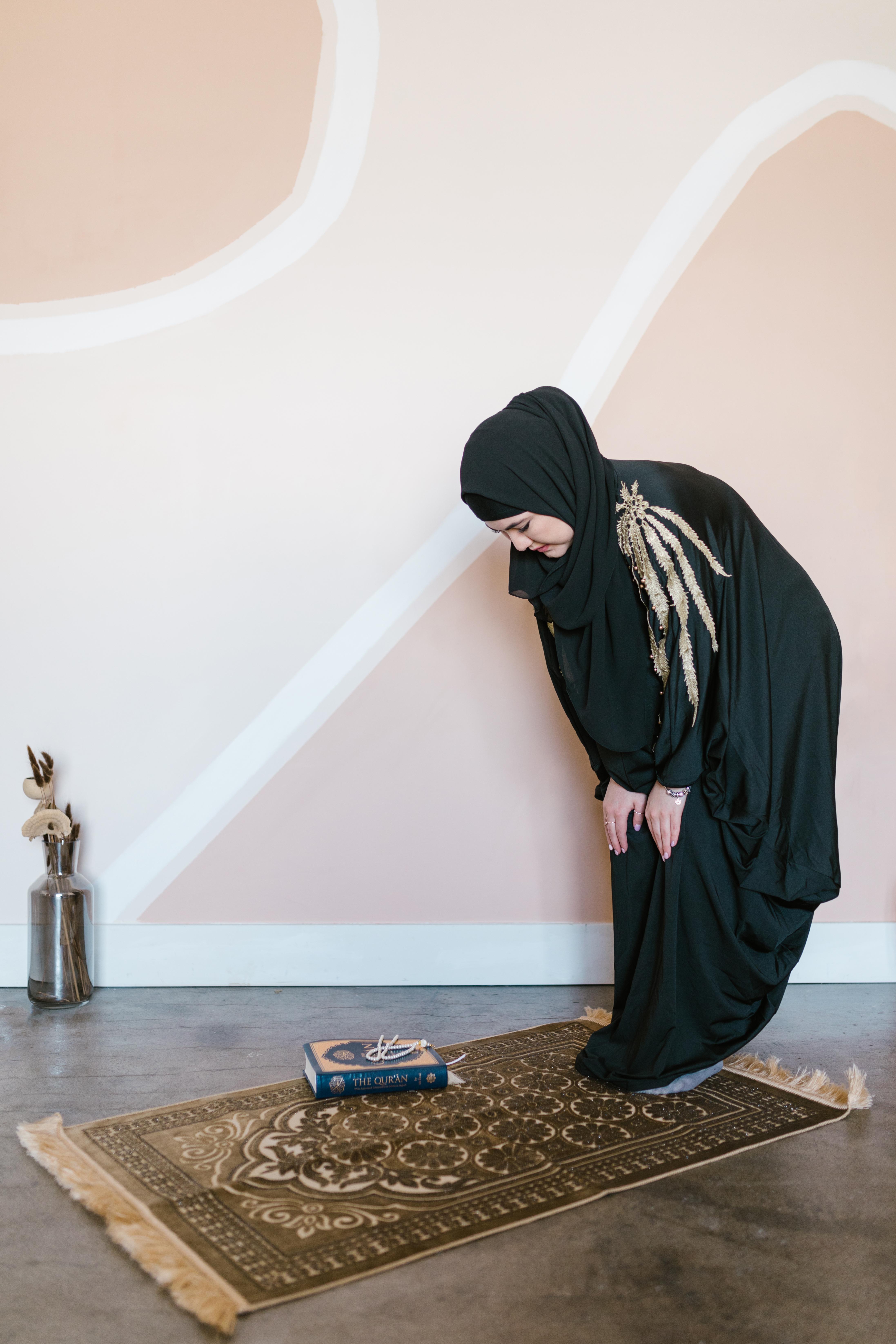 woman in black hijab standing on brown wooden floor