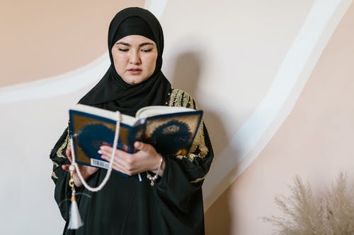 Woman in Black Hijab Holding A Holy Islam Book