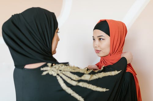 Woman in Black Hijab Standing Face to Face With Woman In Orange Hijab