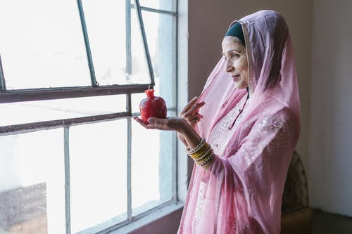 Woman in Pink and White Floral Dress Wearing Blue Hijab Holding Red Glass Bottle