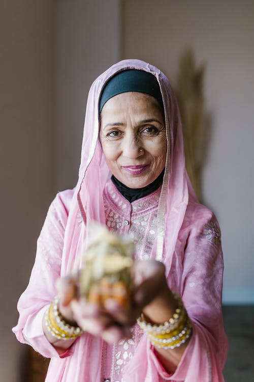 Woman in Pink and White Hijab Holding Fruit