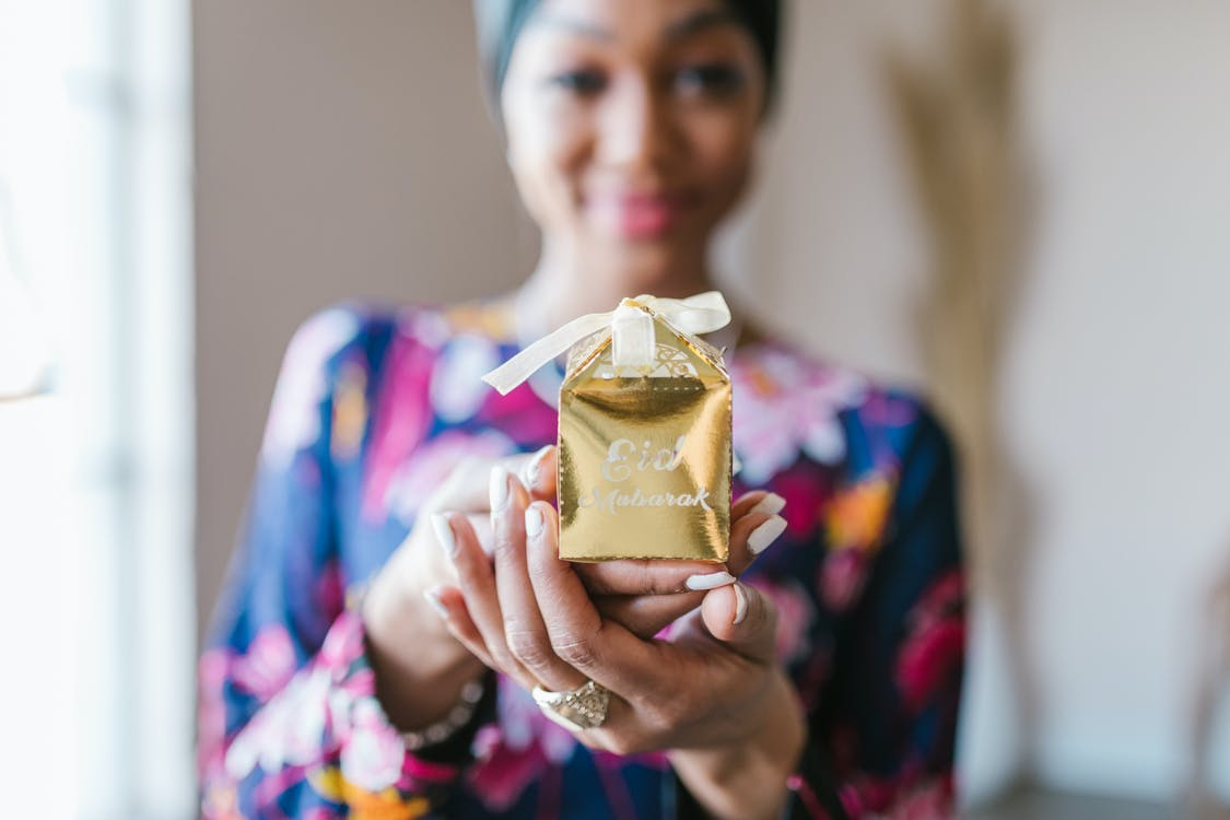 Woman in Blue and Pink Floral Dress Holding Gold Gift Box
