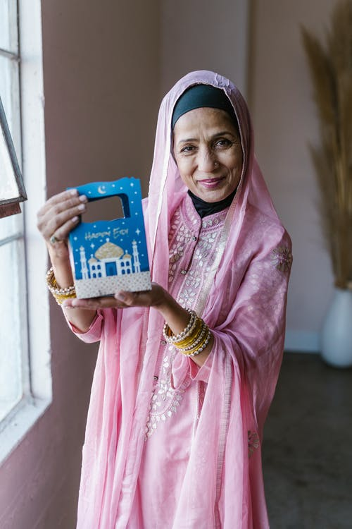 Woman in Pink Hijab Holding Blue and White Box