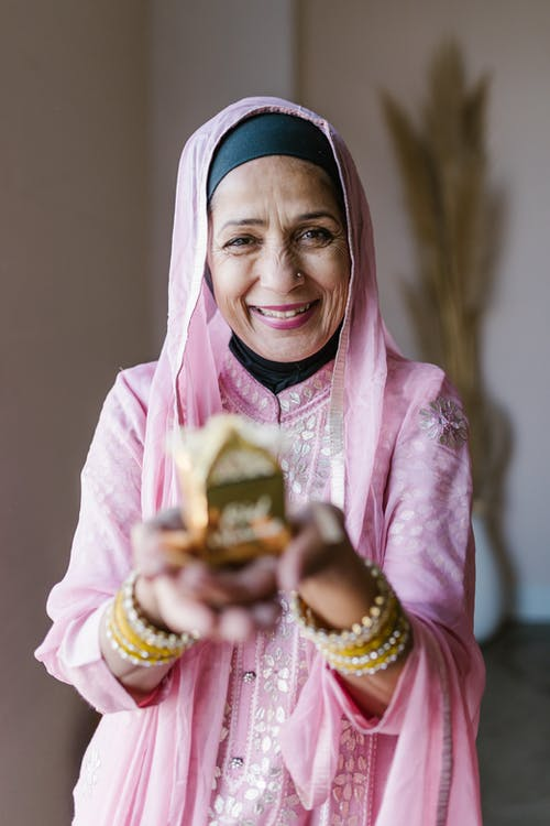 Smiling Woman in Pink and White Hijab Holding Gold and Gold Trophy