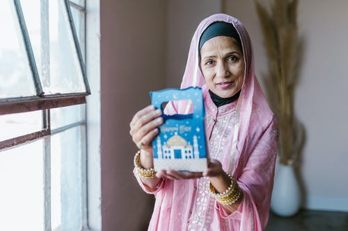 Woman in Pink Hijab Holding Blue and White Plastic Pack