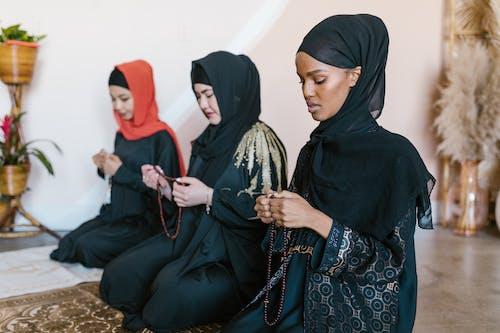 3 Women Wearing Hijab Sitting on Brown Carpet