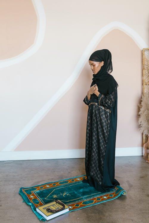 Woman in Black Hijab Standing on Rug