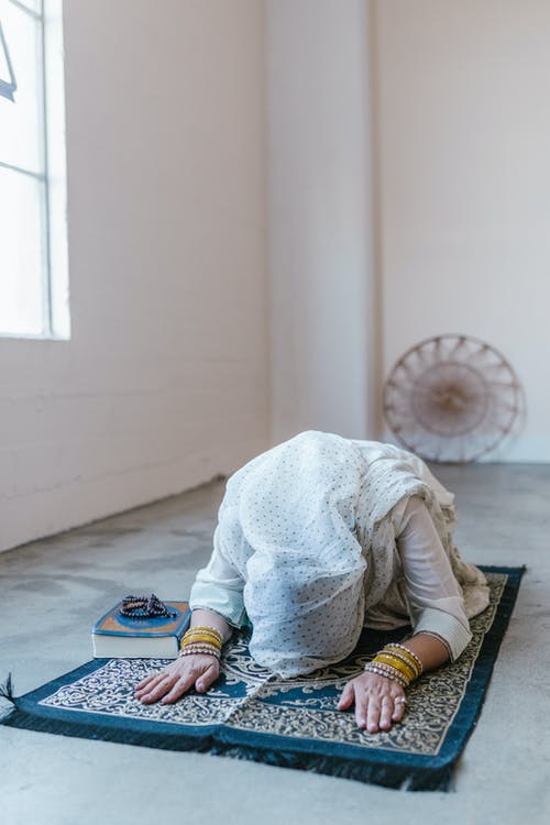 Woman in White Hijab Praying In A Room