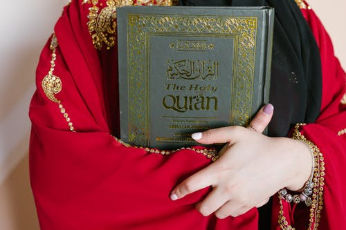Person Holding A Holy Quran Book