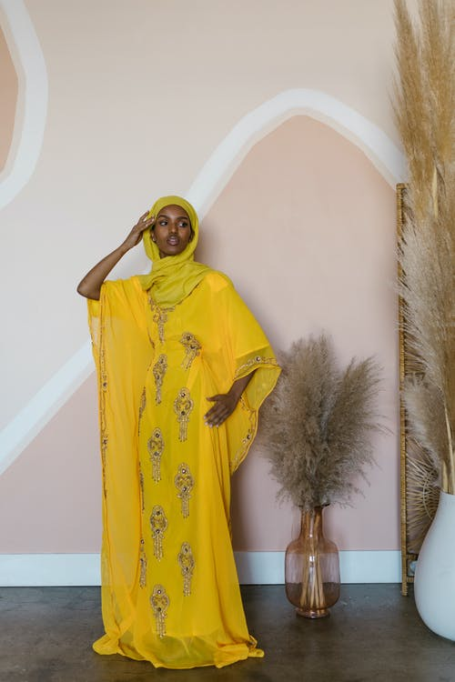 Woman in Yellow Hijab Standing Beside Green Christmas Tree