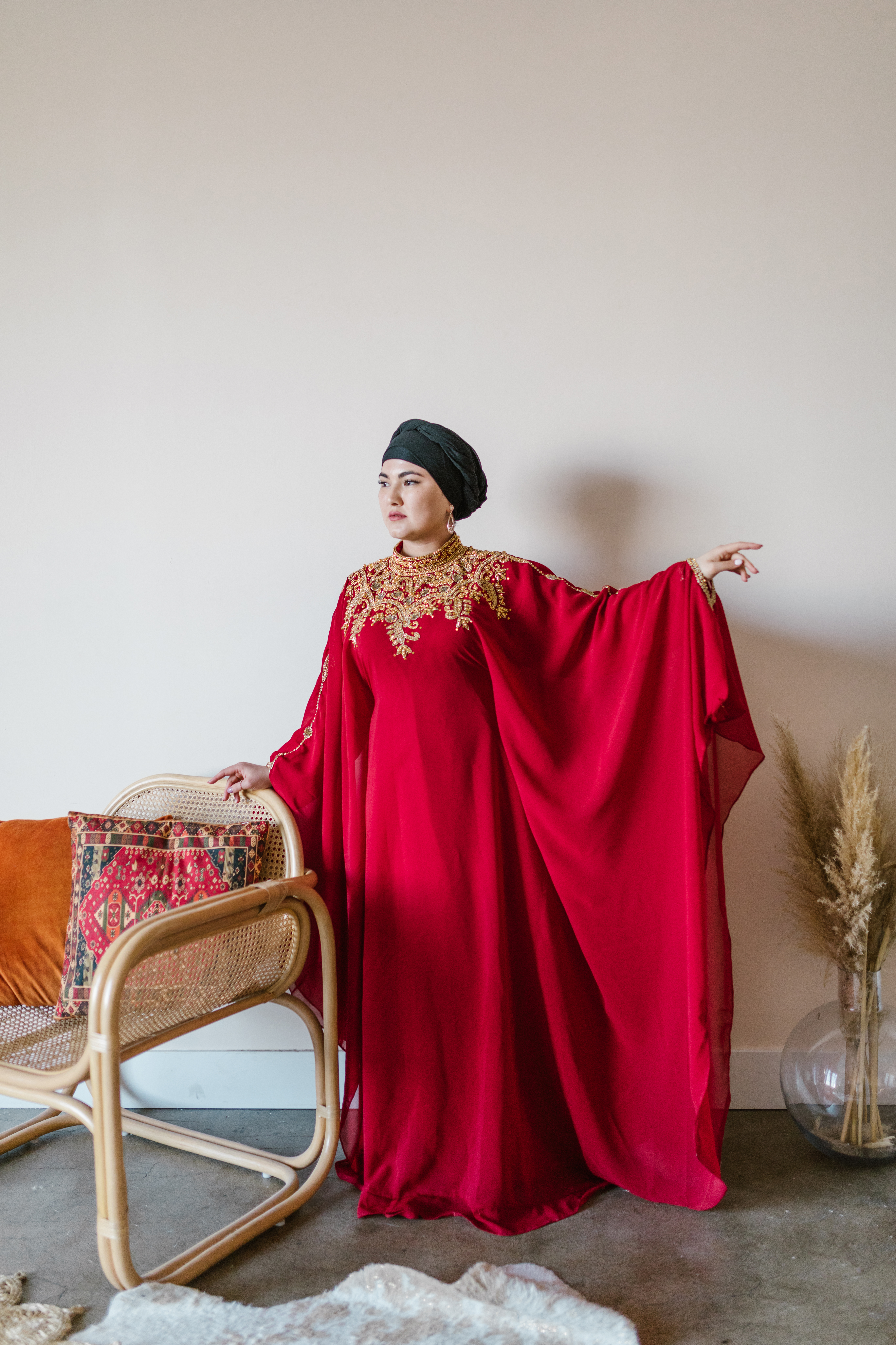 woman in red hijab standing near brown and white floral sofa
