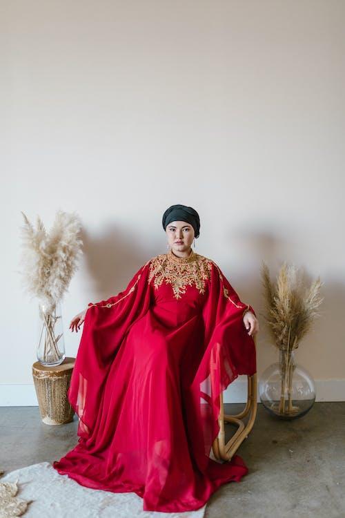 Woman in Red Long Sleeve Dress Standing Beside Brown Wicker Basket