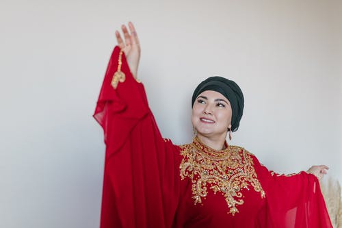 Woman in Red Hijab and Gold Floral Dress