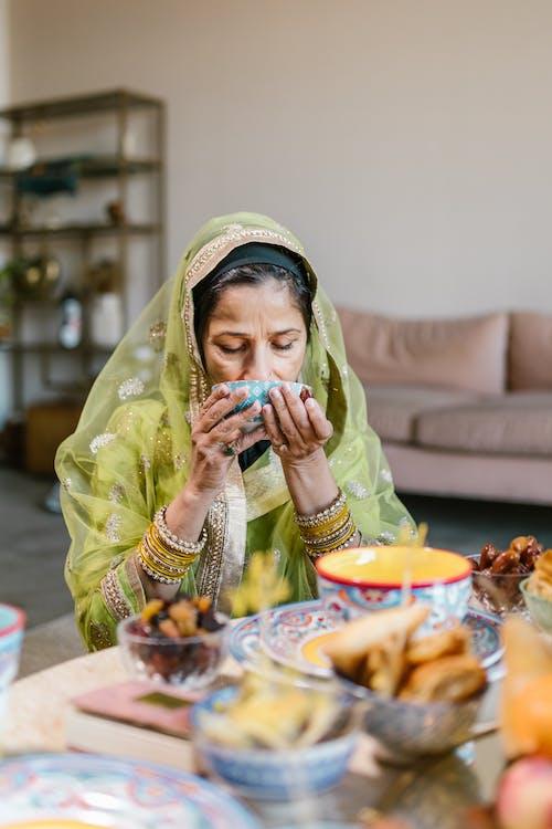 Woman in Green Hijab Sitting on Chair