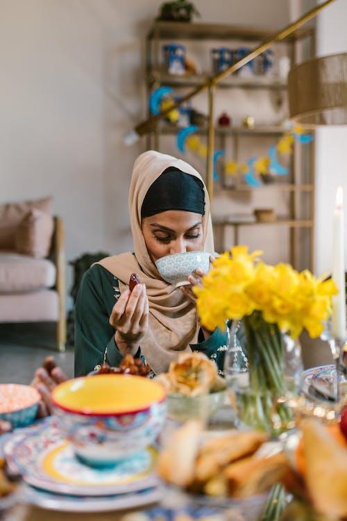 Woman in Gray Hijab Holding White Ceramic Bowl