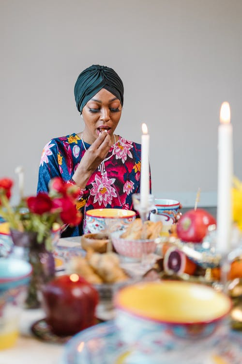 Woman in Blue and Pink Floral Shirt Sitting Beside Table With Food