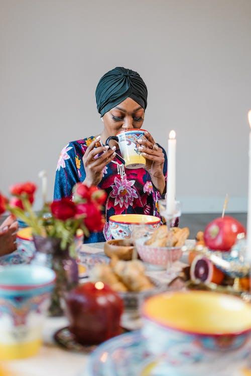 Woman in Blue Hijab Holding White Ceramic Mug