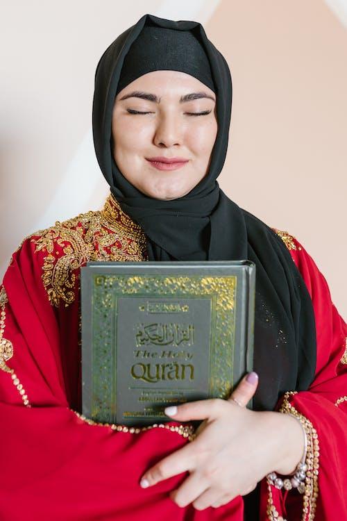Woman in Black Hijab Holding Green Book