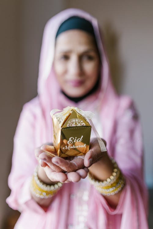 Woman in Pink Hijab Holding Brown Chocolate
