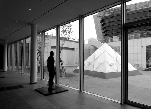 Mannequin in modern building against glass wall