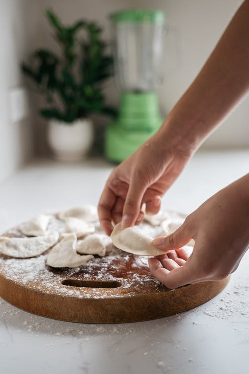 Person Holding White Dough on Wooden Cutting Board