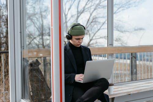 A Man Using a Laptop while Wearing Headphones