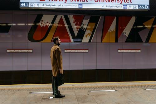 A Man Waiting at a Subway Platform