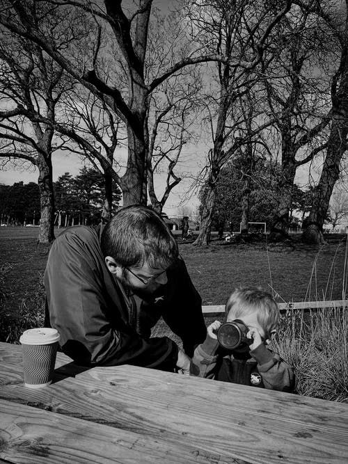 Father and son sitting drinking tea in spring park