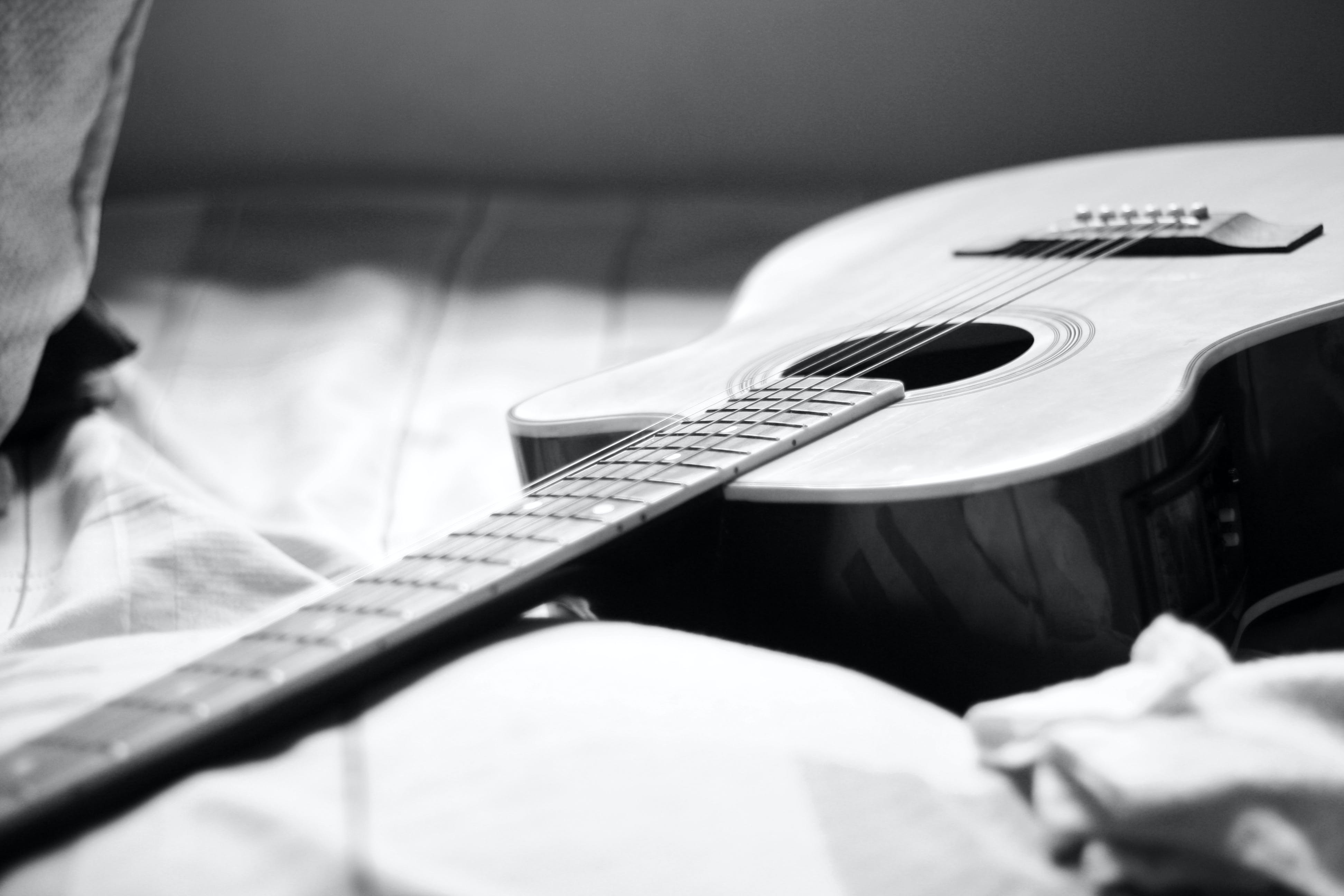 Gray Scale Photography of Acoustic Guitar on Bed