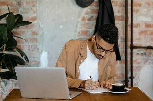 Man in Brown Long Sleeves Polo Writing on a Notebook