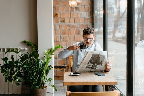 Man in Gray Sweater Reading a Newspaper
