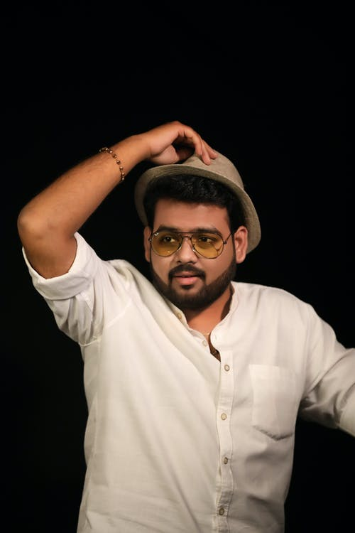 Young bearded ethnic male in trendy sunglasses and hat looking away on black background