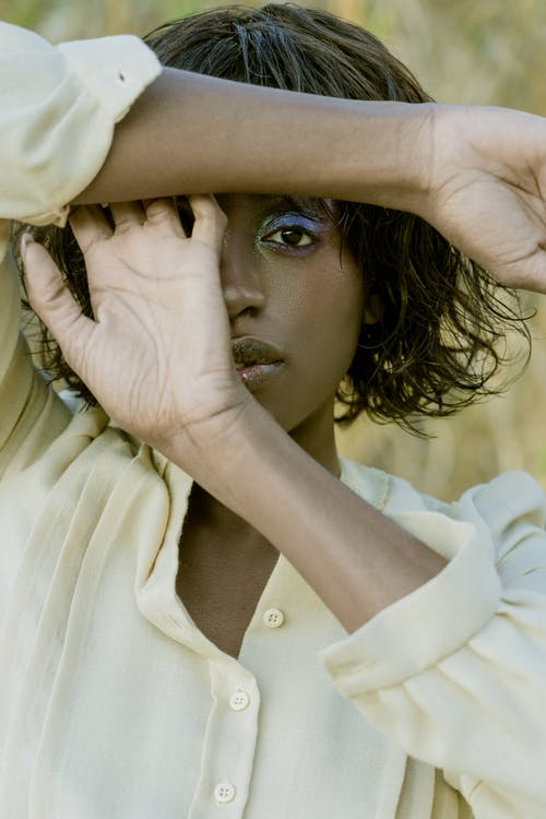 A Woman Covering Half of Her Face with Her Hands