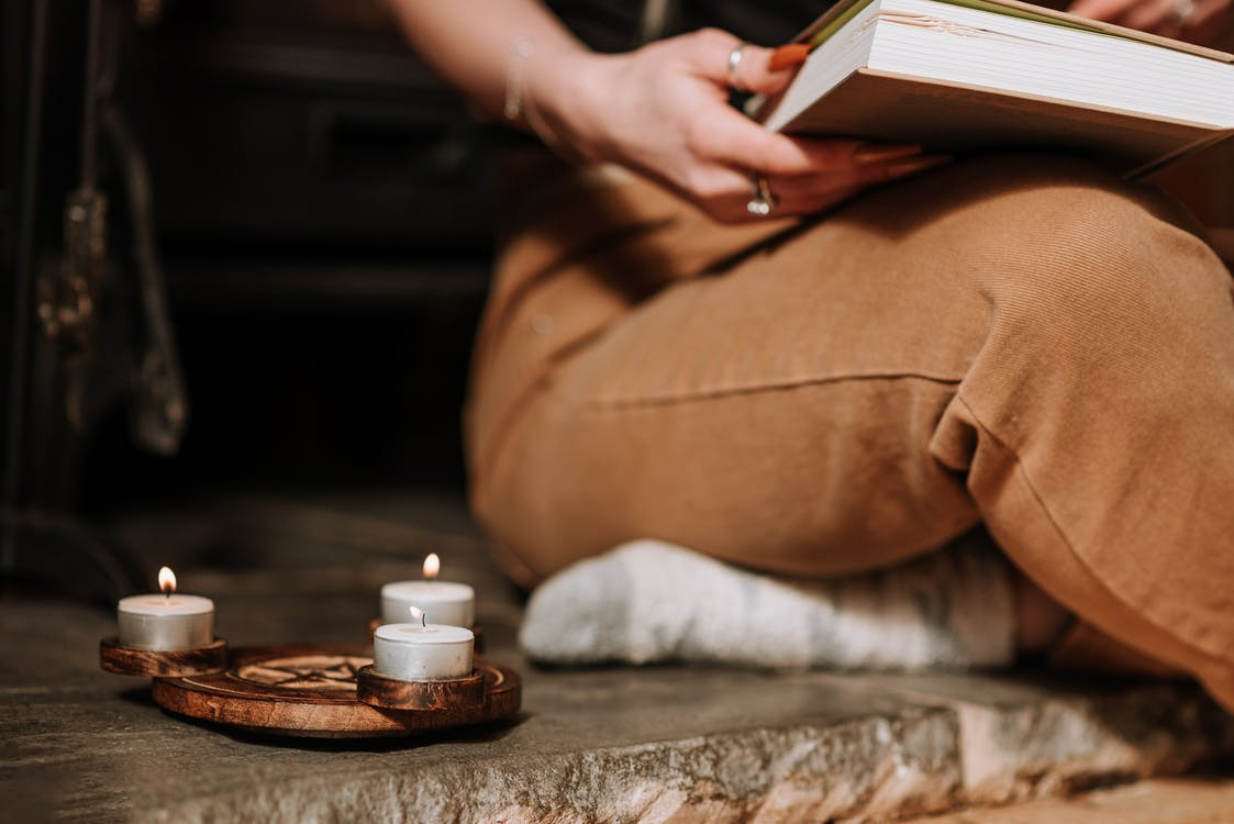 Unrecognizable mysterious female with book sitting in aged house near small burning candles placed on metal surface with spiritual symbol