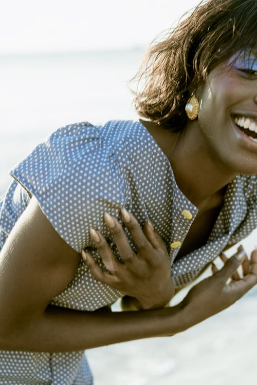A Woman in Blue and White Polka Dots Dress Smiling