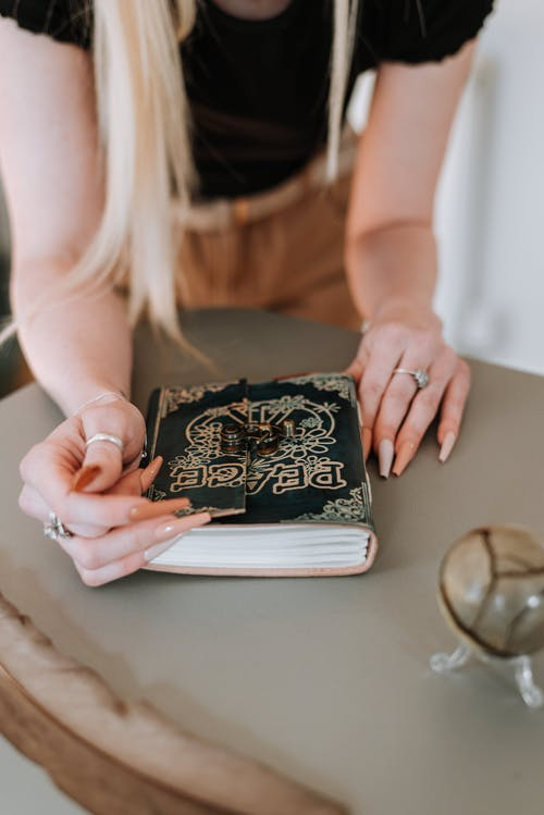 Soothsayer at table with thick notebook with word peace